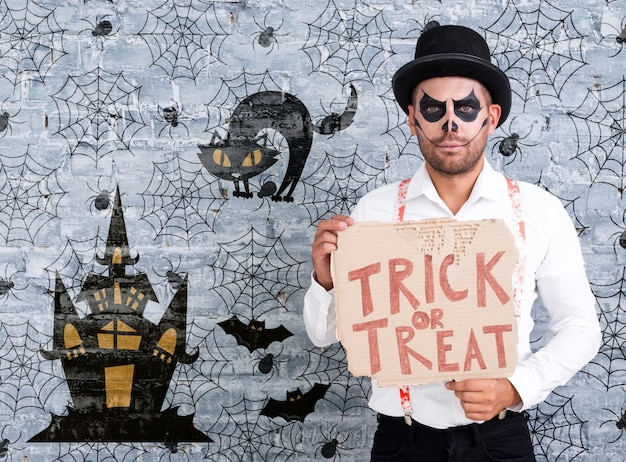 Man met make-up met een kaart met trick or treat belettering voor halloween