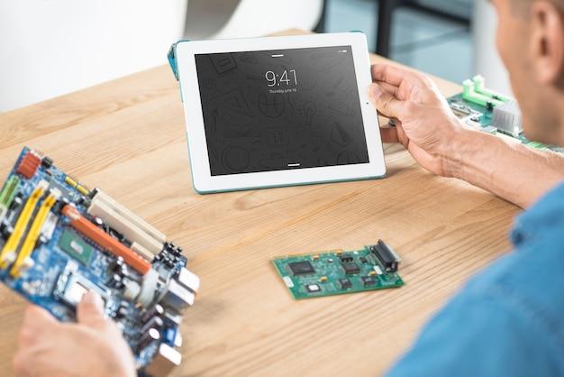 Man met moederbord en tablet