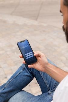 Man op straat met telefoon met app