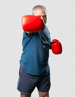 Man van middelbare leeftijd ponsen zichzelf met bokshandschoenen