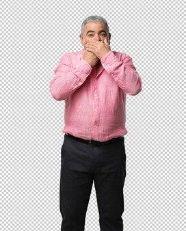Man van middelbare leeftijd voor de mond, symbool van stilte en onderdrukking, en probeert niets te zeggen