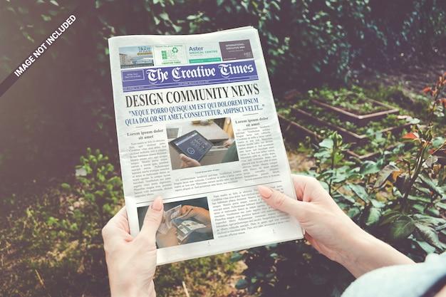 Mani che tengono il mockup del giornale