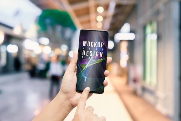 Mani del modello facendo uso dello smartphone nella sera sulla strada dei negozi della città