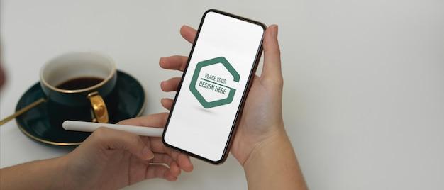 Mani dello studente utilizzando smartphone mockup in ufficio