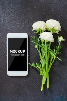 Manichino di schermo dello smartphone e fiori bianchi su