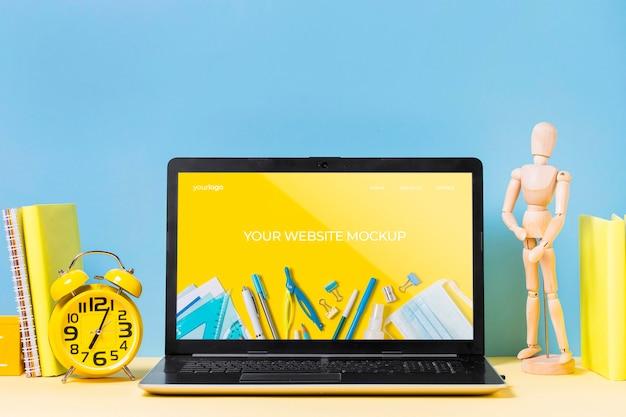 Maniqui de madera y laptop con maqueta