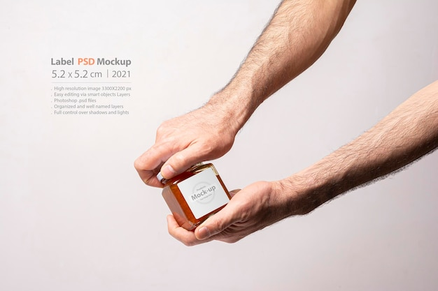 Mannelijke handen die een deksel van een zoete worteljamfles openen