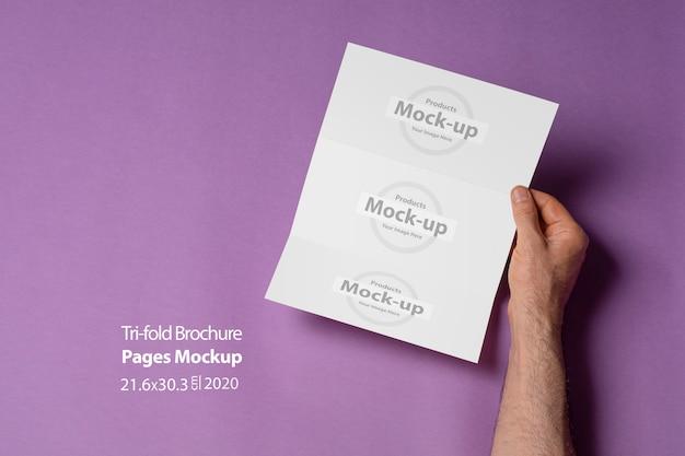 Mannelijke handen die een gevouwen brochure met blanco pagina's op purpere lijst houden