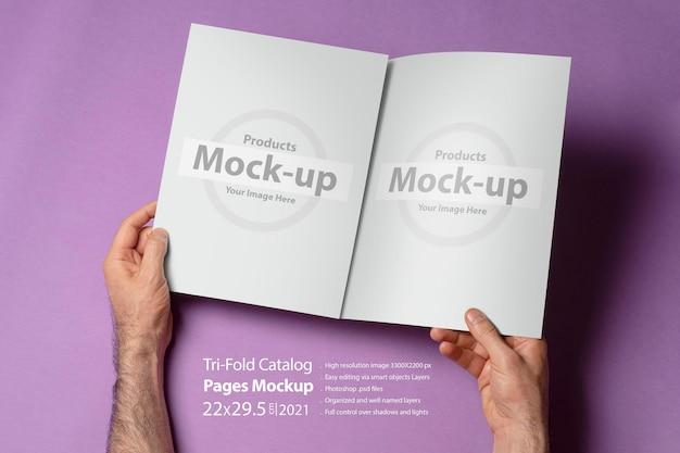 Mannelijke handen met een geopende driebladige catalogus met blanco pagina's