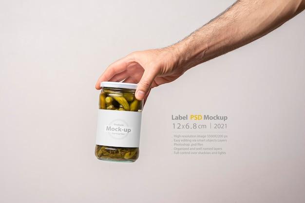 Mannelijke handen met een ingemaakte komkommer glazen pot