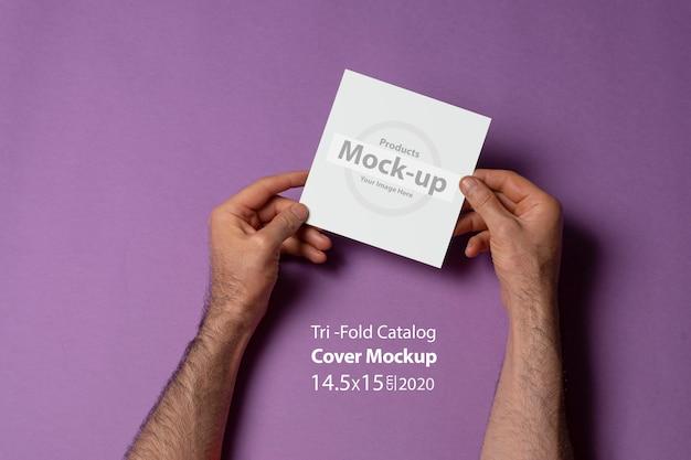 Mannelijke handen met een vierkante tri-fold catalogus met blanco omslag op paars oppervlak