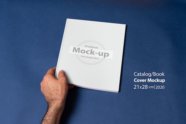 Mannenhand met een gesloten catalogus of tijdschrift met lege omslag
