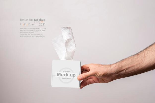 Mannenhand met een kubusvormig tissuedoosmodel