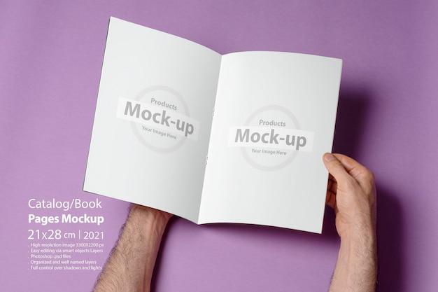 Mannenhand opende een a4-catalogus op paarse achtergrond