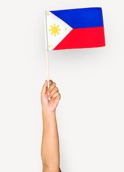 Mano che tiene bandiera filippina isolato