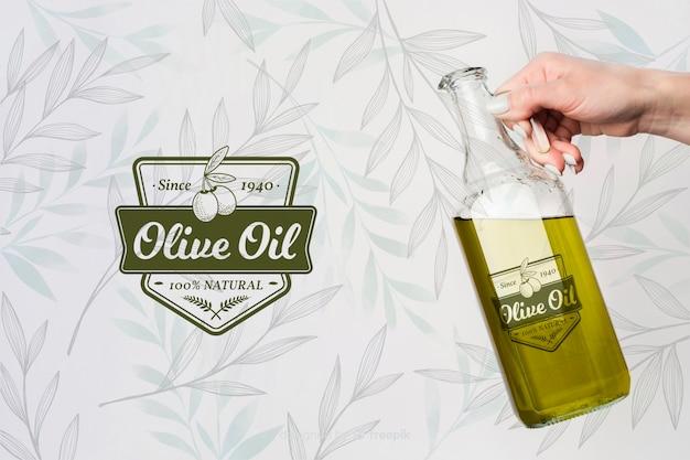 Mano che tiene l'olio d'oliva