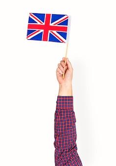 Mano che tiene la bandiera britannica isolato