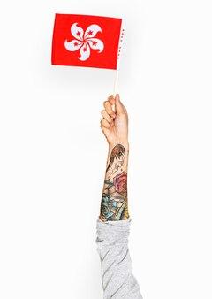 Mano che tiene la bandiera di hong kong isolata