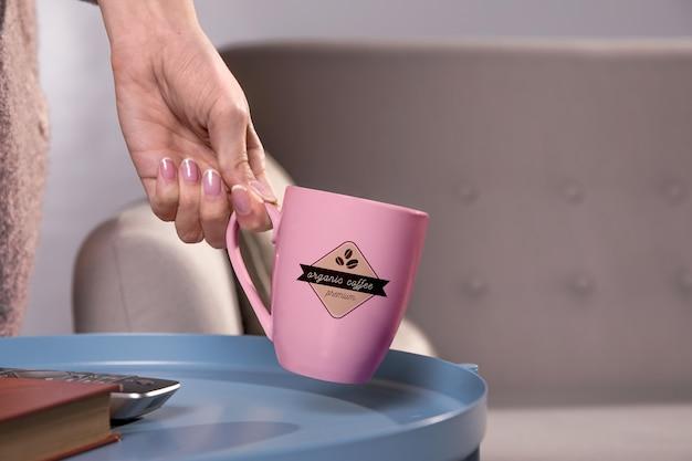 Mano del primo piano che tiene tazza da caffè rosa