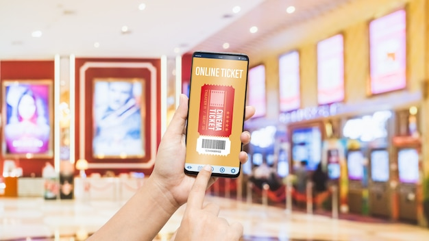 Mano del telefono cellulare del modello facendo uso dello smartphone per il concetto online dei biglietti del cinema