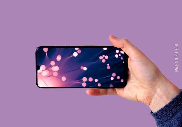 Mano derecha sosteniendo maqueta de smartphone horizontal