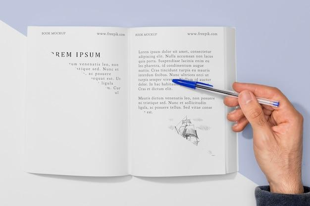 Mano di vista superiore che tiene la penna sopra il modello di libro aperto