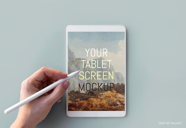 Mano escribiendo en maqueta de tableta