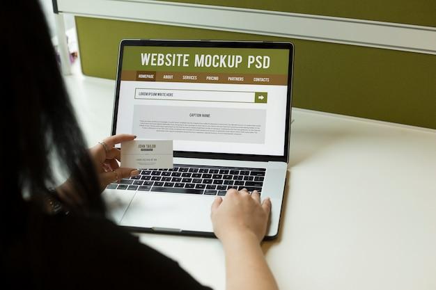 Mano femenina de la muchacha que sostiene la tarjeta de visita y que usa maquetas del ordenador portátil psd
