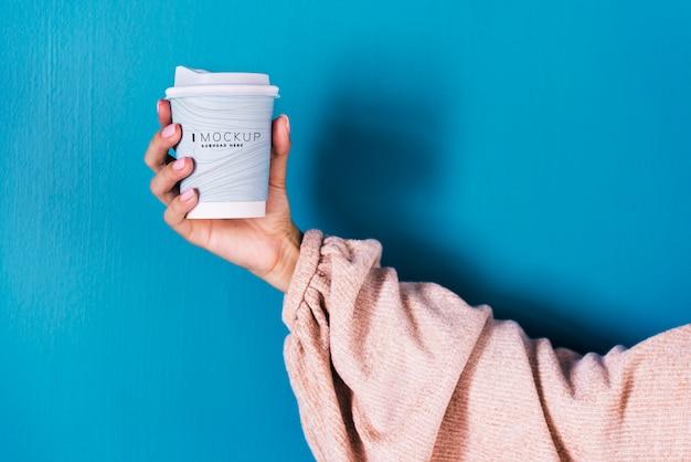 Mano femminile che tiene un modello di tazza di caffè