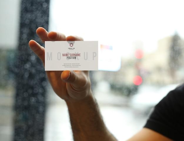 Mano de hombre sosteniendo maqueta de tarjeta de visita psd