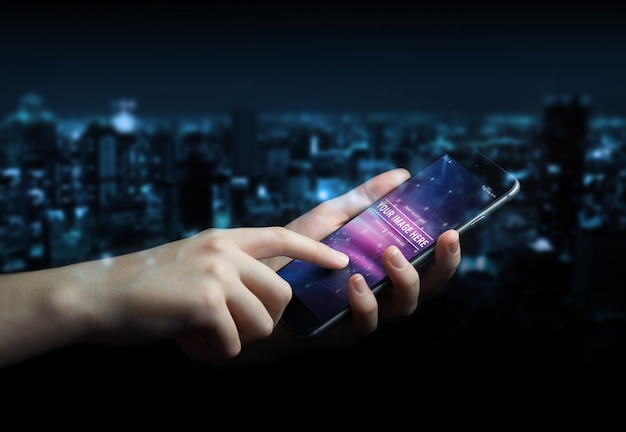Mano de mujer con smartphone moderno en maqueta oscura