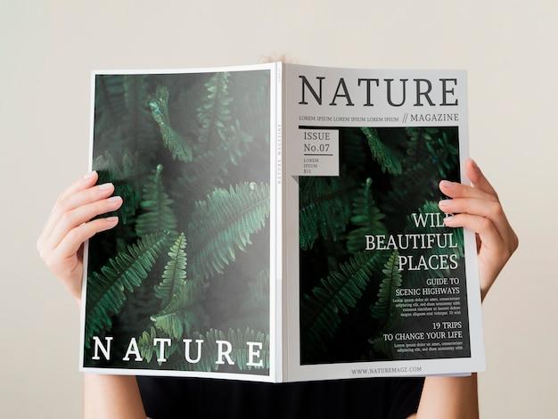 Mano de mujer sosteniendo una revista de naturaleza simulacro
