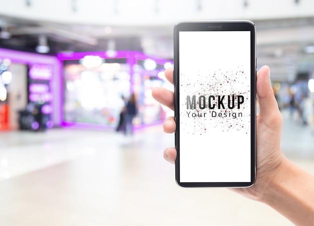 Mano de mujer sosteniendo y tocando smartphone negro con maqueta de pantalla en blanco para su diseño en desenfoque abstracto grandes almacenes o centro comercial.