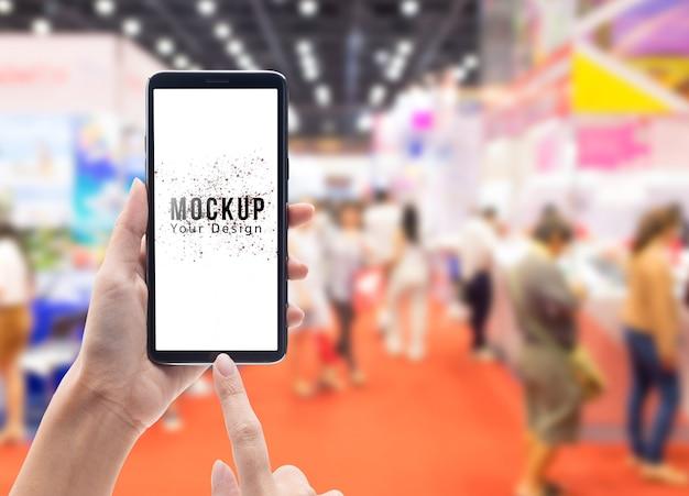 Mano de mujer sosteniendo y tocando smartphone negro con maqueta de pantalla en blanco