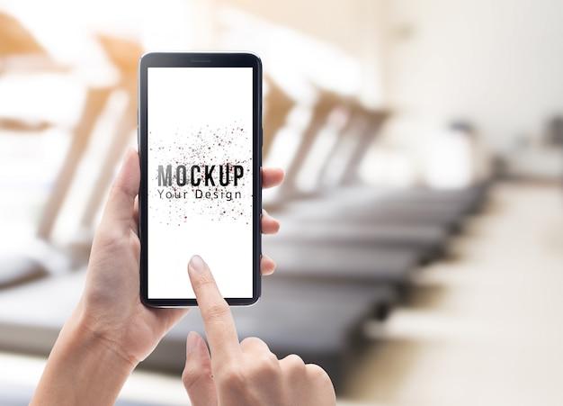 Mano de mujer sosteniendo y tocando smartphone negro con plantilla de maqueta de pantalla en blanco
