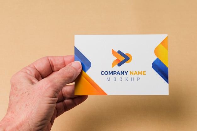 Mano de primer plano que sostiene la maqueta de la tarjeta de visita