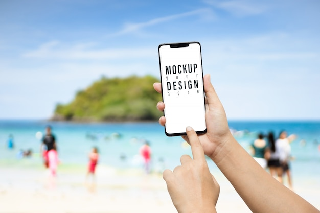 Mano que sostiene el teléfono inteligente en frente de la playa