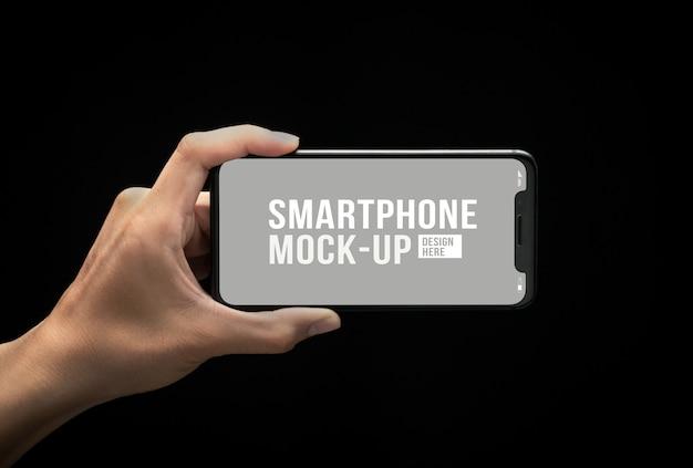 Mano que sostiene el teléfono inteligente moderno con plantilla de maqueta de pantalla para su diseño.