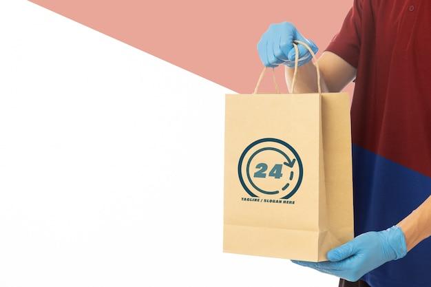 Mano del repartidor en guantes médicos con plantilla de maqueta de bolsa de papel artesanal.
