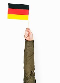 Mano sosteniendo la bandera alemana