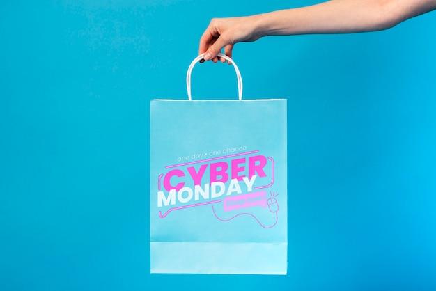 Mano sosteniendo una bolsa de papel de lunes cibernético