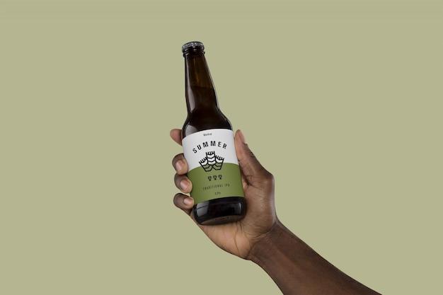 Mano sosteniendo la botella de cerveza maqueta