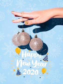 Mano sosteniendo colgando bolas de plata y feliz año nuevo cita