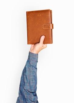 Mano sosteniendo el libro de cuero