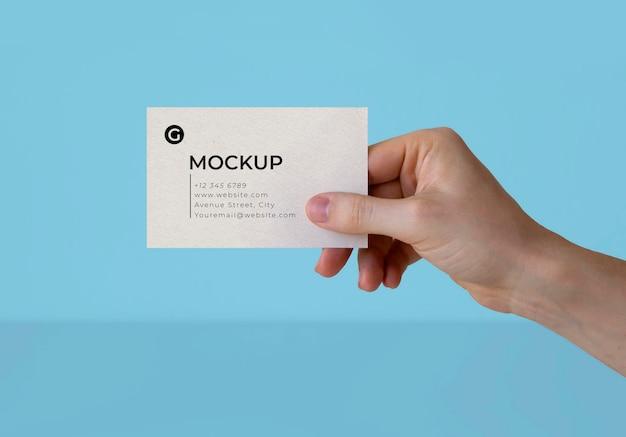 Una mano sosteniendo una maqueta de tarjeta de visita.
