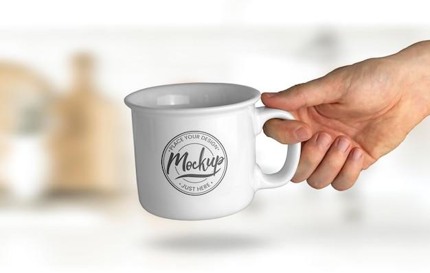 Mano sosteniendo una maqueta de taza