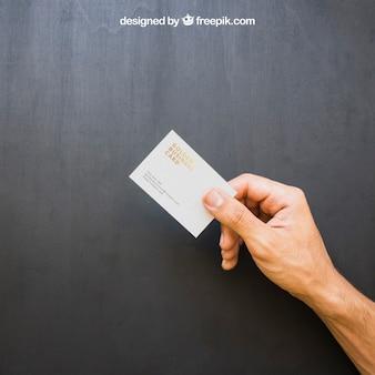 Mano sosteniendo tarjeta de visita dorada