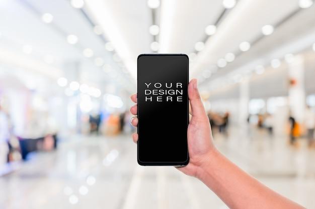 Mano sosteniendo el teléfono móvil con desenfoque pasillo pasillo