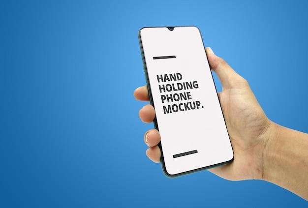 Mano sujetando diseño de maqueta de smartphone aislado