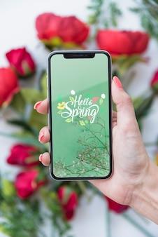 Mano sujetando maqueta de smartphone encima de flores